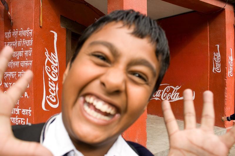 Мальчик у стены с логотипом Coca-Cola