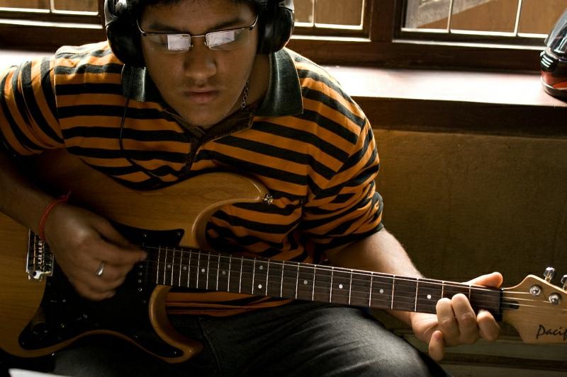 Студент класса гитары с отражениями в очках