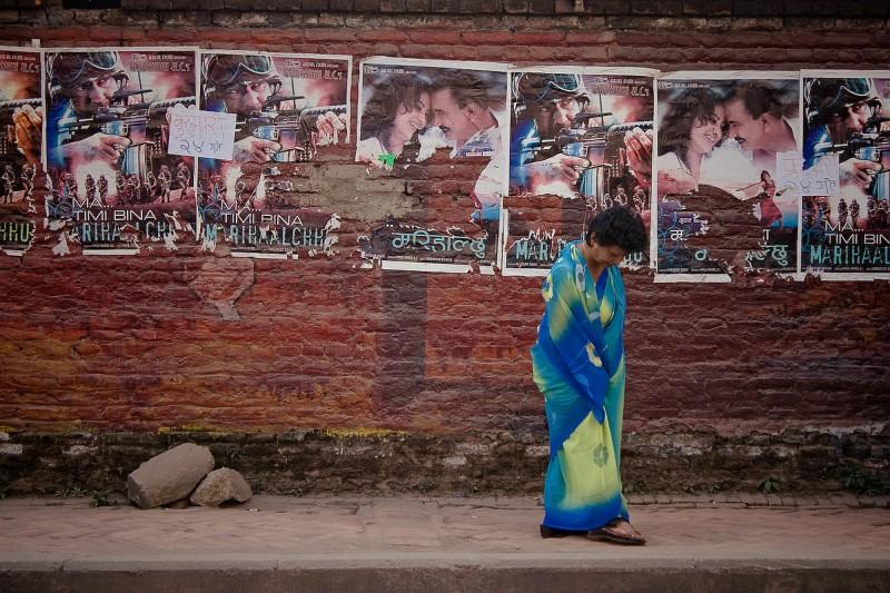 Женщина у стены с постерами