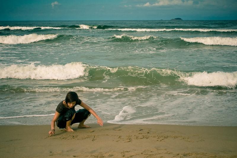 Девочка, пишущая на песке